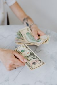 """person counting money to ask themselves """"Should I file bankruptcy?"""""""