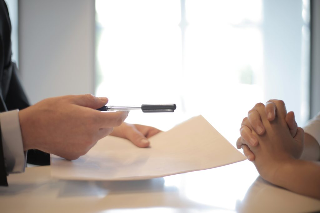 people exchanging papers and pens as a part of what can a client expect