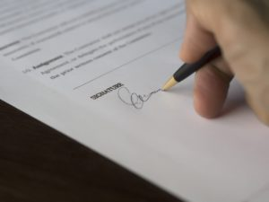 person signing contract with the help of the best contracts and business disputes attorney in columbus, ga